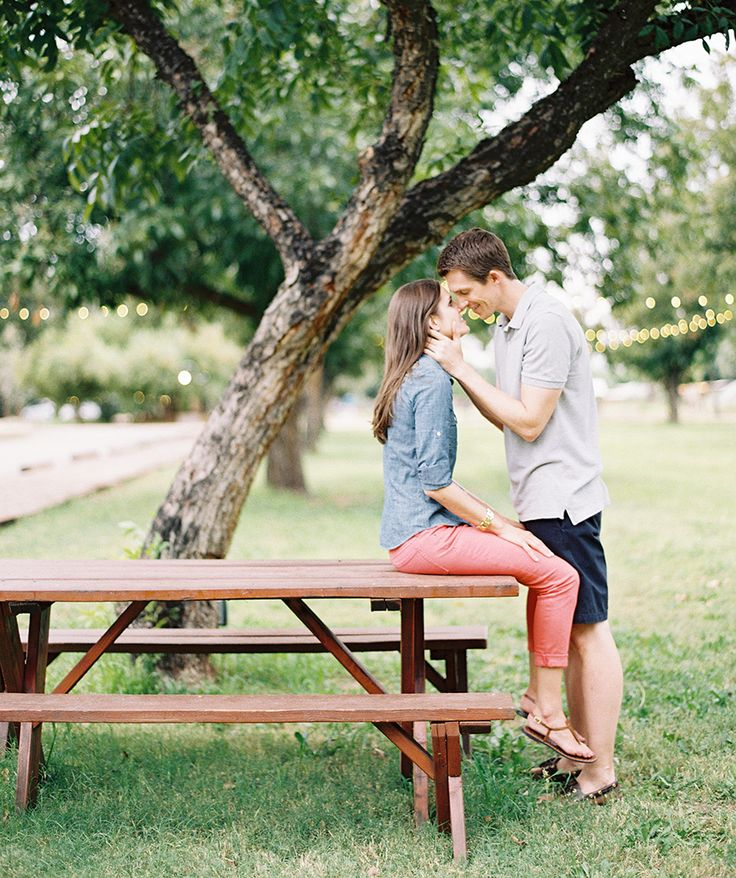 Loving couple in an outdoor engagement shoot -- posing with a picnic table