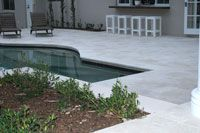 Travertine Linen Tumbled unfilled Ashlar pattern surround paving.The Pool Tile Company - Swimming Pools Brisbane
