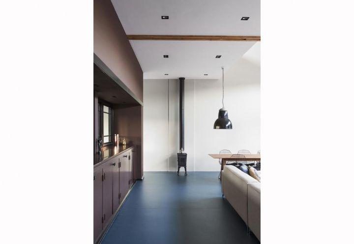 Una parete attrezzata con mobili su misura in metallo – materiale prediletto dallo studio R U I M – separa la sala dalla cucina. Il living è riscaldato da una stufa in ghisa vintage, acquistata in un negozio di antiquariato di Amsterdam