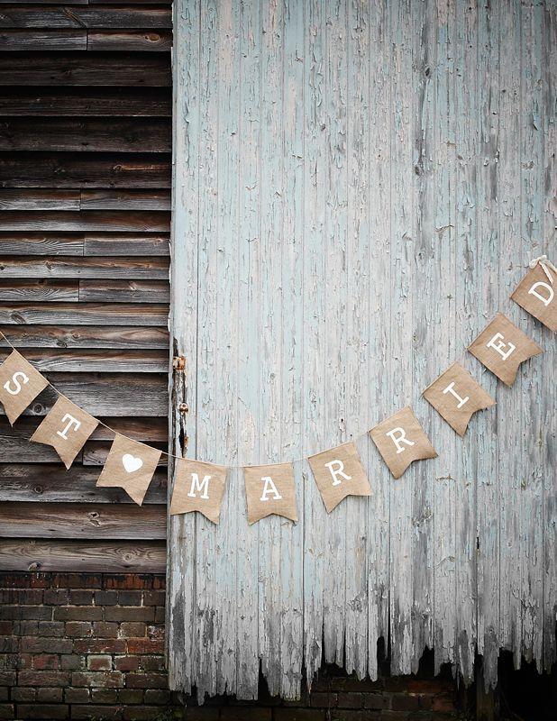 """Decorazione in stile rustico chic in tela di iuta, con bandierine che compongono la scritta """"Just Married"""" stampata in bianco, e fiocchi in pizzo alle due estremità. Bellissima da appendere all'esterno della chiesa o all'ingresso del locale che ospiterà la cerimonia."""