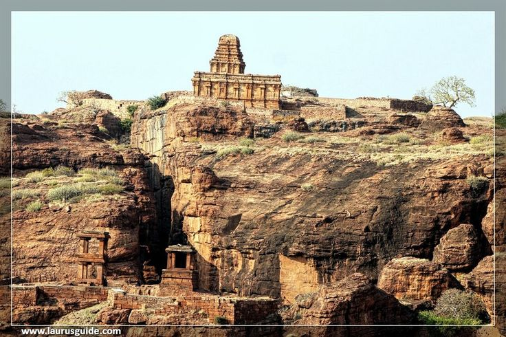 Nestled atop a cliff, the Badami Fort lies opposite to the famous Badami Caves. The fort's location commands a magnificent view of the Badami town and its splendid structures.  The Badami Fort was built in the Chalukyan style of architecture. The fort is surrounded by double fortification walls. The structures within the fort offer a glimpse of the architectural grandeur prevalent during the Chalukyan reign. The entrance of the fort is guarded by a statue of Nandi, Lord Shiva's bull.