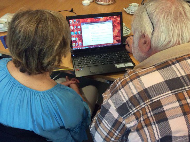 Vapaaehtoinen atk-opastaja Teuvo neuvoo Myllypurossa senioreita tietotekniikan saloihin.