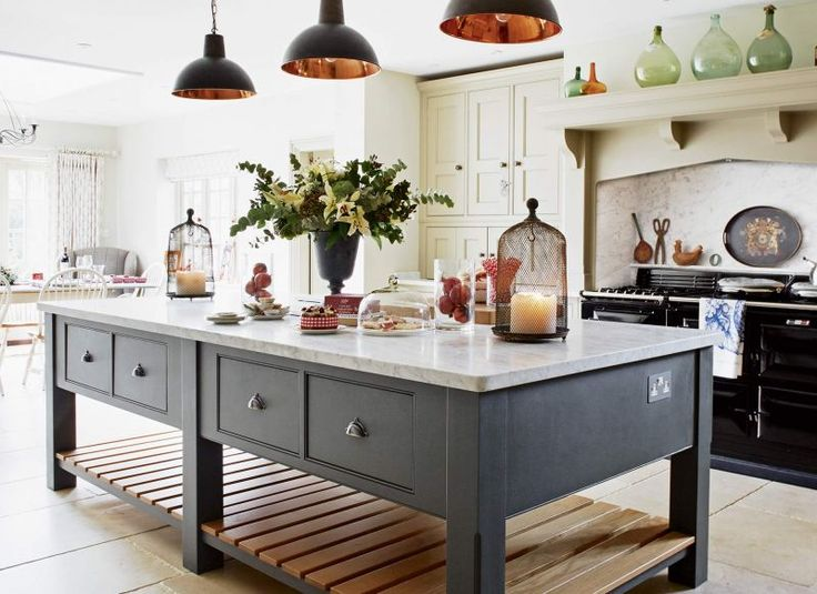 Bring a contemporary edge to a classic country kitchen with chic modern light fittings. The owners have chosen industrial-style, copper-lined pendants in painted black to contrast with the traditional cabinets. Sink, plate rack and wall and baseline units are brought together by wood panelling to create a cohesive dresser-like bank of storage. Their decision to go for a marble worktop with upstand is a practical choice for a sink that lacks a traditional tiled splashback.