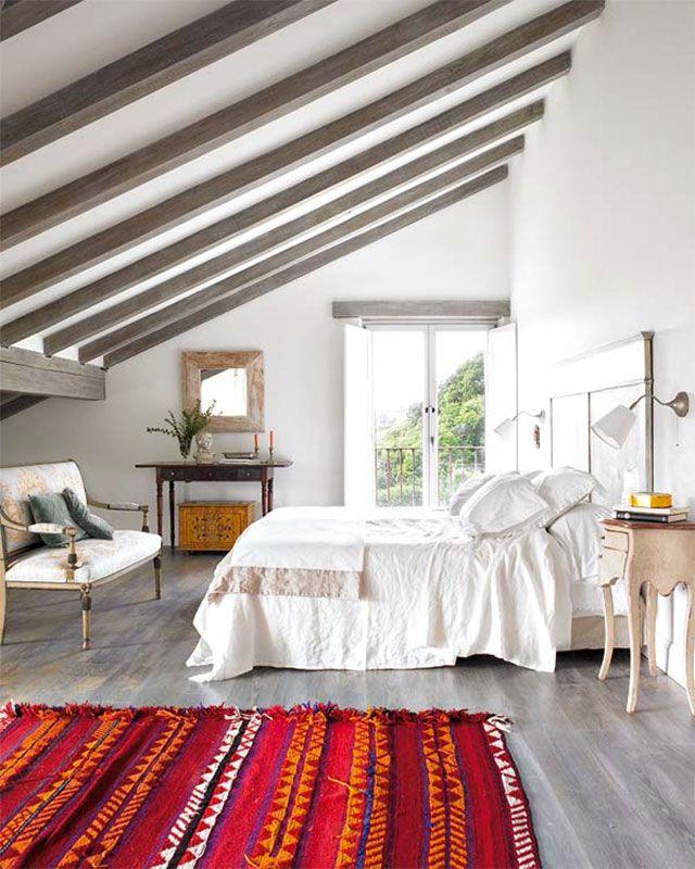 Cama con cubrecama blanco, dormitorio con piso laminado y alfombra roja con diseño de grecas