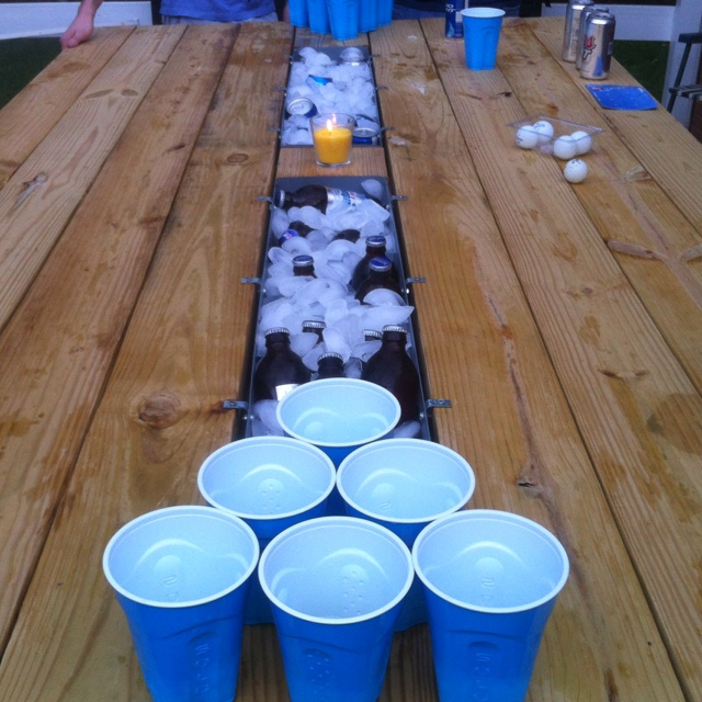 beer pong table with bottles on ice in the center. the bounce rule would have to take a raincheck.