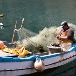 A fisherman comfortably repairing a net !