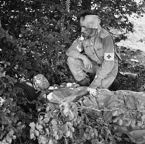 West Nova Scotia Regt medical personnel wounded after Canada's last skirmish with the Italian Army before Italy capitulated to the Allies on September 8th. Captain A.W. Hardy, the Medical Officer with the West Novas lays on stretcher, next to stretcher-bearer Pte. W.E. Dexter, who was wounded in the head, near Cittanova, Italy, 8 September 1943. (Photo by Terry Rowe, LAC a115198)
