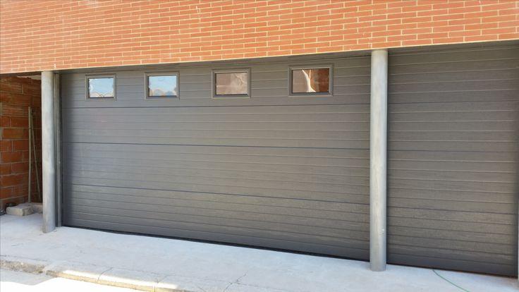 Puerta seccional en color RAL 7024 con panel acanalado rugoso de tipo woodgrain con 4 ventanas insertadas. Fijo lateral a juego con la puerta seccional principal.