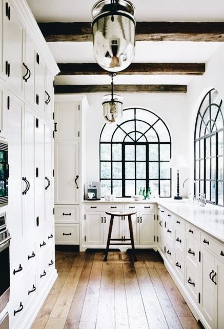 All white kitchen is beautifully accented with black hardware and windows