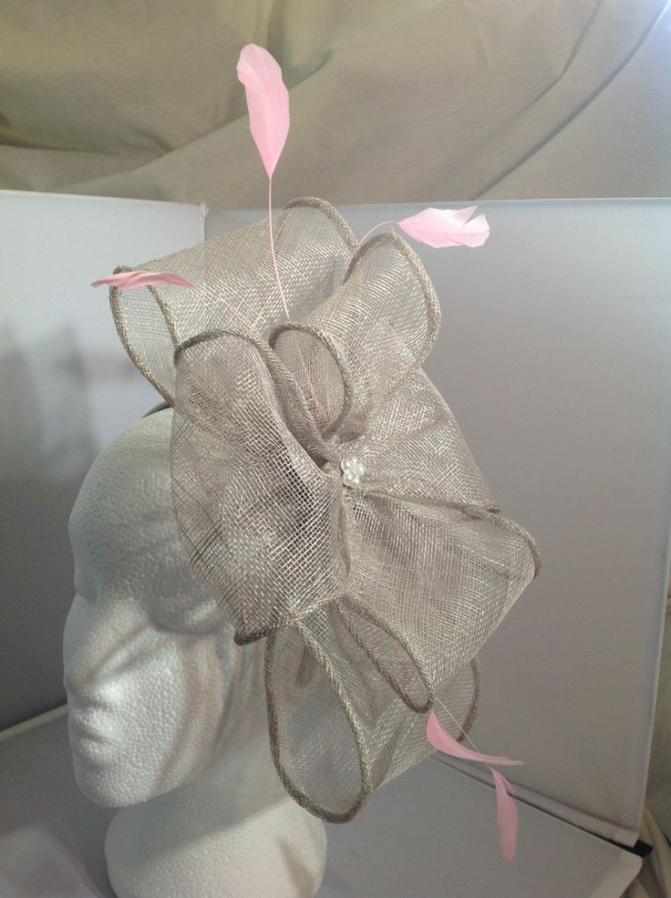 A fascinator by fascinators by Julie the Clara is an extra large fascinator on a silver head band an extra large silver sinamay bow supports a large silver sinamay flower with a pearl flower centre piece and baby pink feathers to finish. $140 AUD. Found in the Silver collection on the website.