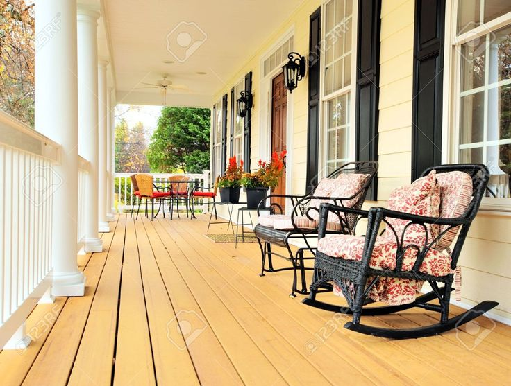 A White Wooden Rocking Chair Is Sitting On The Front Porch Stock ...