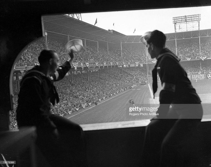 Two sailors watch a Brooklyn Dodgers game from the press box before shipping out. Photo taken on opening day at Ebbets Field in Brooklyn, New York.