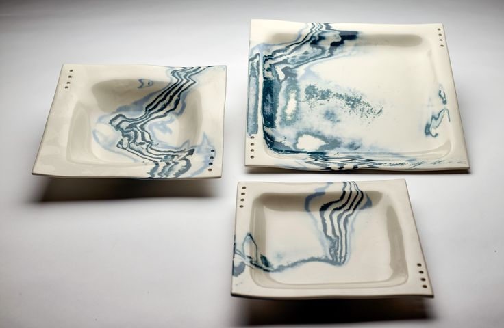 Place setting of dinnerware with blue and green lines through porcelain.