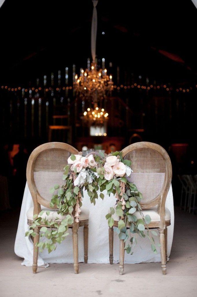 Unir les chaises des mariés par des fleurs pour reproduire le lien qui les uni