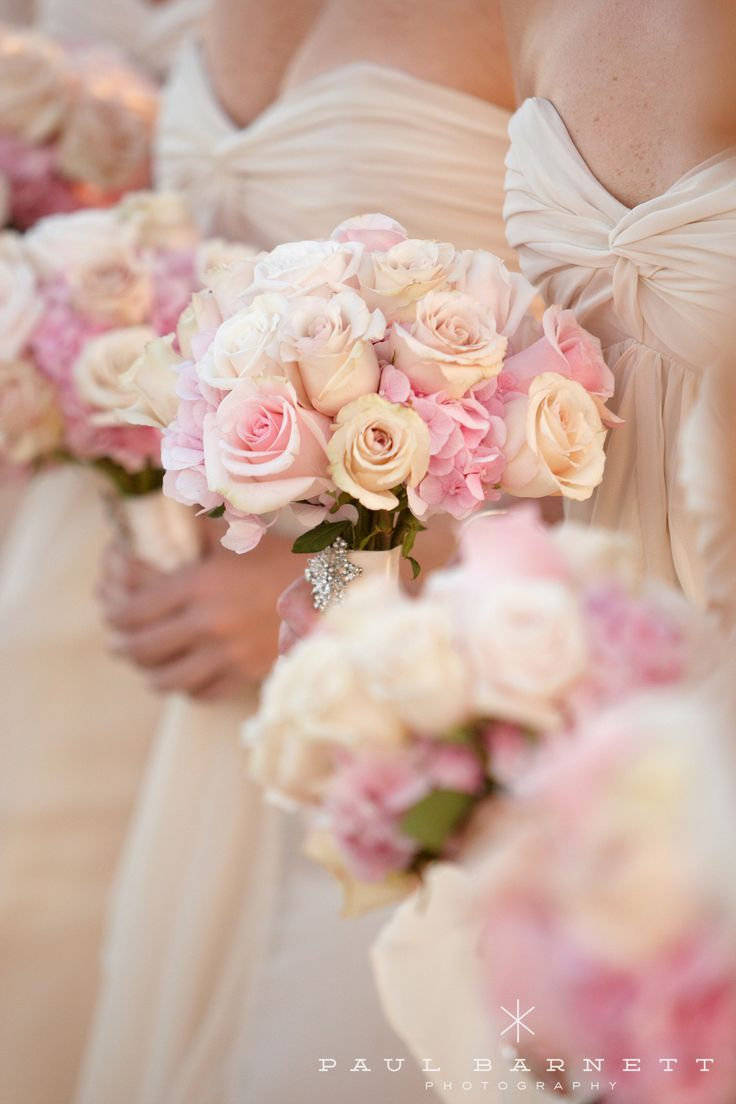 pretty pinks and creams roses look gorgeous against the ivory bridesmaids dresses during the ceremony