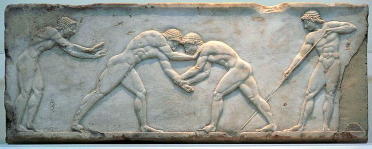 A Greek marble relief depicts two men grappling with each other. The man on the right is grabbing the other man's left arm with two hands, while the left man's free arm grabs the right man's left shoulder. Two more men watch from the sides, with the one on the right holding a long rod or stick. 510–500 BC