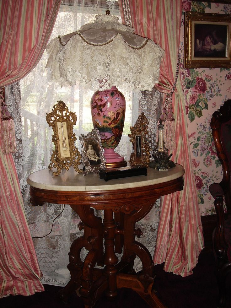 An iconic Victorian nook, with well-carved, marble top tea table, lace curtains and lamp shade, drapes puddling on the floor, rose-dappled wallpaper, and objects on the table.  I love the frames on the table!  I would put this palette and amount of lace in a bedroom.