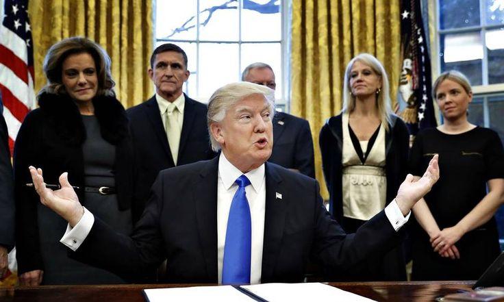 Præsident Donald Trump forsvarer sit omstridte indrejseforbud og hævder, at det var computerproblemer, der skabte kaos i amerikanske lufthavne. Her ses han ved underskrivelse af et dekret i Det Ovale Kontor. Foto Alex Brandon/AP.