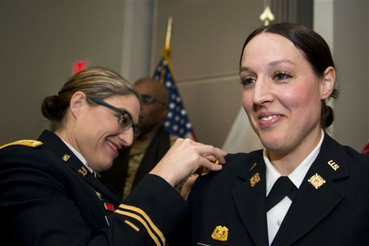 Iowa Army National Guard Maj. Jill Finkel, left, pins on Massachusetts Army National Guard Maj. Molly Alesch's new gold oak leaf rank insignia at a promotion ceremony at Hanscom Air Force Base, Mass., March 17, 2017. Finkel and Alesch are sisters and their youngest sister, Army Spc. Kristen Alesch, who serves in the Tennessee National Guard, also attended the promotion ceremony. Massachusetts Army National Guard photo by Sgt. 1st Class Whitney Hughes