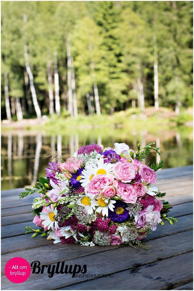 Vakker brudebukett i hvitt, rosa, lilla og grønt. Buketten er laget av både ville blomster, hageblomster og kjøpte blomster.   Bryllupsinspirasjon.no