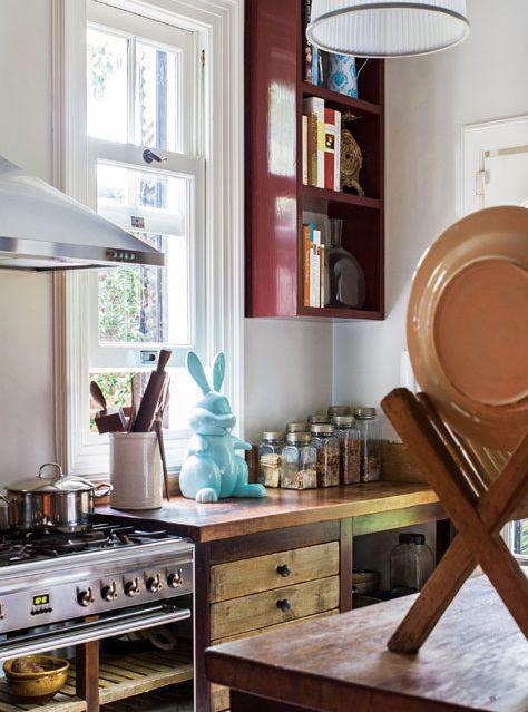 Cocina de una casona con muebles de madera, conejo celeste de cerámica y paredes pintadas de blanco.