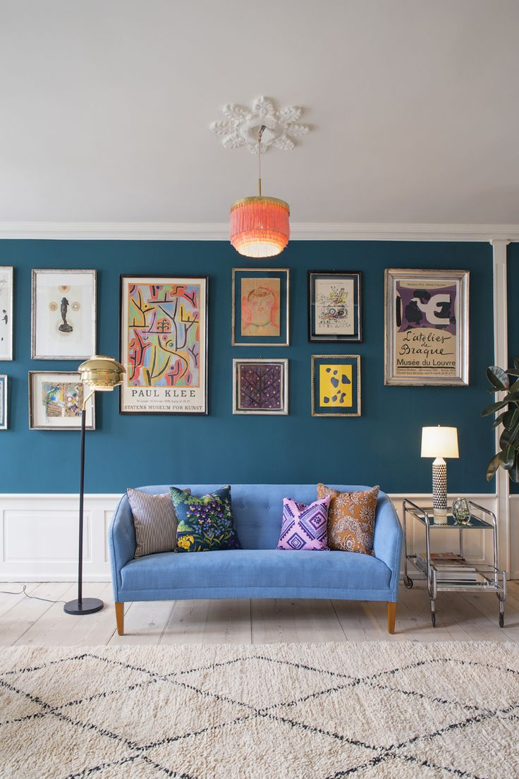 Dark blue walls adorned with colourful artwork and prints the peacock blue velvet sofa and