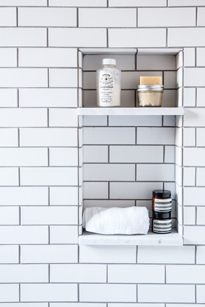 A compact bathroom that has been beautifully designed, using a mix of art deco & industrial inspiration … white subway tiles + dark grout, great brass fixtures, floating concrete basin, geometric tili