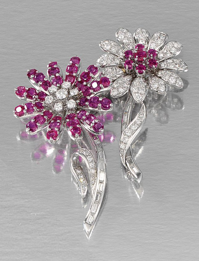 RUBY AND DIAMOND DOUBLE-CLIP BROOCH.  Designed as a pair of stylised flowers, the petals respectively set with mixed-cut rubies, brilliant- and single-cut diamonds, highlighted by brilliant-cut diamond and circular-cut ruby centres, to stems and leaves set with brilliant-, single- and baguette stones, detachable from central fitting.