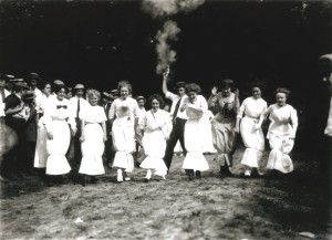 Eight women participate in a hobble skirt race. Starter gun has just been fired by man in straw boater hat. (1912)