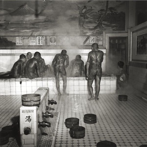 """""""Public Bath"""" Silver gelatin print 1946 Full body tattoos are often associated with the Japanese criminal gang, the Yakuza. This type of public bath is known as onsen, where people can bathe in a natural spring, and they provide a forum where the Yakuza can display their tattoos. Steam was believed to heighten the colors of the tattoos."""