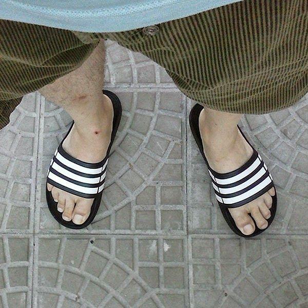Homem usando chinelo slide adidas Duramo