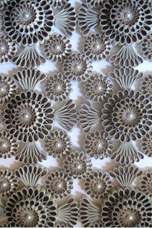 Patterns on a wall hanging by Katherine Wardropper. Leather, silk satin and Swarovski pearls.