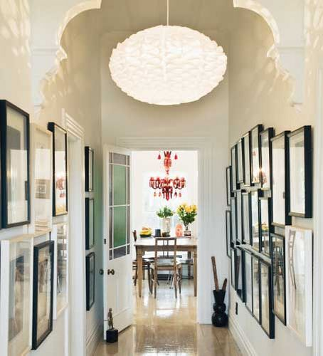 "Hallway space with gallery walls and anchored by two dramatically different light fixtures | ""Your Home and Garden"", New Zealand shelter magazine (Design and photography unknown)"