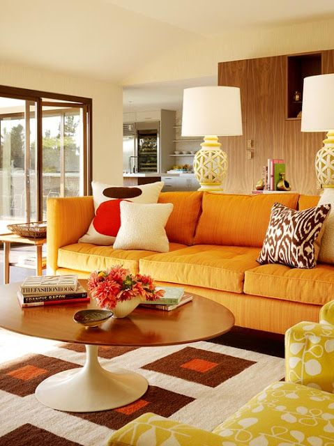 Orange sofa with patterened cushions and tulip coffee table. A Seventies inspired living room look. More decorating ideas at www.redonline.co.uk