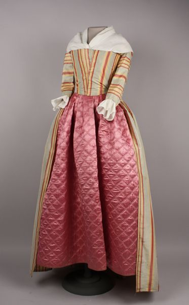 1785-1795 Gown, 18th century gown, striped blue, yellow, and pink silk rep. Gown is open down center front, slits on each side to accomadate separate pockets or to pull the skirt through to create a polonaise effect. A separate set of slits closer to the front have been stitched shut. Other signs of alterations are present, specifically at the waistline and the center back. The hem has been let out. Bodice is lined with glazed linen. Back of bodice comes to a sharp center point. Sleeves end…