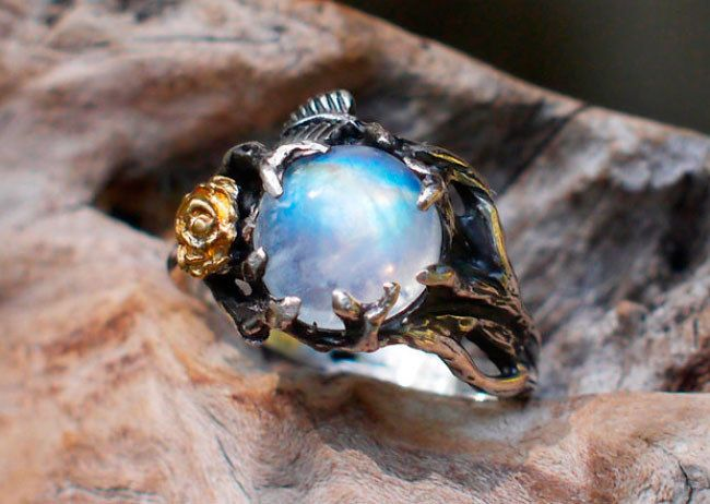 "A moody moonstone set inside a precious <a href=""https://go.redirectingat.com?id=74679X1524629&sref=https%3A%2F%2Fwww.buzzfeed.com%2Ftreyegreen%2Fpretty-engagement-rings-diamond-stone&url=https%3A%2F%2Fwww.etsy.com%2Flisting%2F251585355%2Fsterling-silver-rainbow-moonstone-ring&xcust=4588624%7CAMP&xs=1"" target=""_blank"">twig and rose band</a> to give a nature lover all the feels."