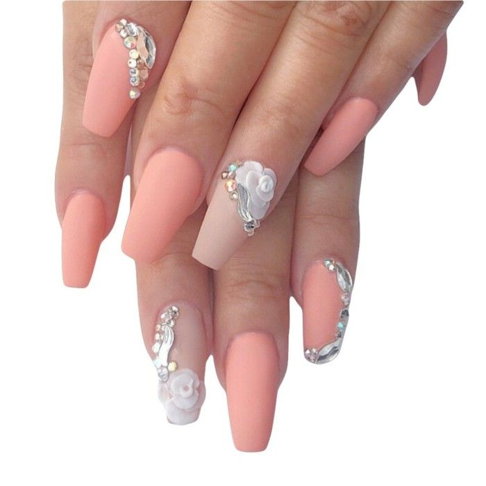 close up of nails in different shades of pale coral pink matte nail polish, four nails decorated with white acrylic flowers or/and rhinestones