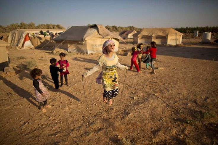 Syrian refugee girl, Zubaida Faisal, 10, jumps rope while she and other children play near their tents at an unofficial tented settlement near the Syrian border on the outskirts of Mafraq, Jordan, on  July 19, 2015.
