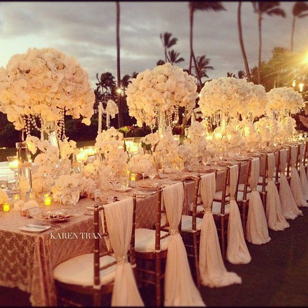 such a beautiful long wedding table design: gold and ivory theme | large white hydrangea and rose centerpieces with hanging crystal garlands | vertical chiffon ivory sashes on chiavari chairs tied with crystal rhinestone bling wrap