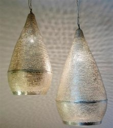 This beautiful pendant light is handcrafted in Egypt. Traditional techniques and craftsmanship are combined with a modern design. The hand hammered brass drops are silver plated and then drilled with delicate patterns. The little holes give the most gorgeous light effect on walls and ceiling.