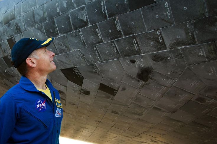 Chris Ferguson, STS-135 commander, examines the thermal tiles of the orbiter after the space shuttle Atlantis completed the final mission of the NASA shuttle program in 2011.