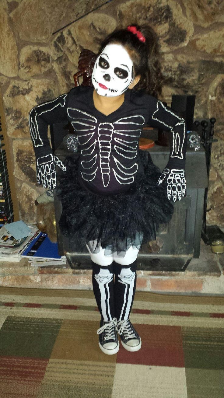 Homemade skeleton costume  used white metallic puff paint for the shirt and drew the face myself. And just to make it a tad girl I came up with the idea to do bright red lipstick with bright red flowers in the hair :)