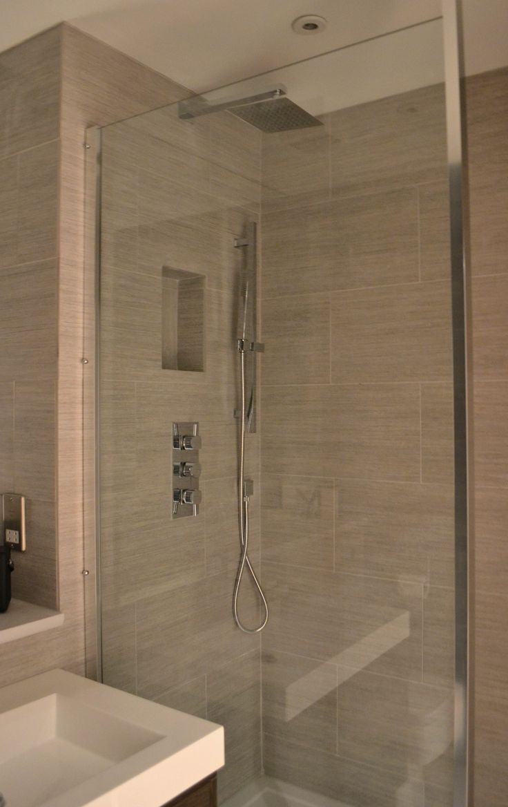 Simple clean lines, storage in the shower area and light tiles to help make a compact space feel spacious