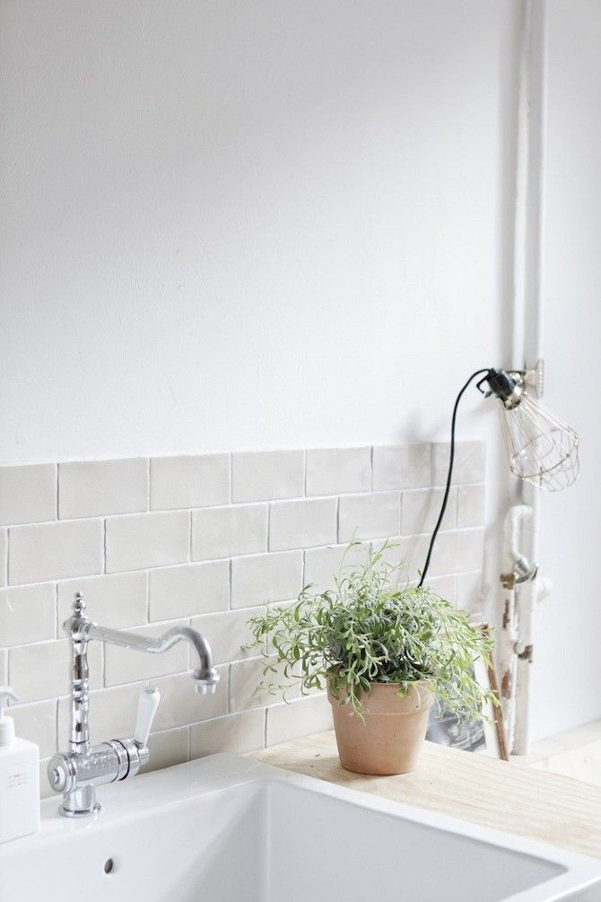 Tile kitchen backsplash and light bulb with wire cage clipped onto pipe in Wiesbaden Apartment by Studio Oink   Remodelista