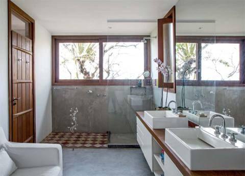 O banheiro fora do padrão, com direito a sofá, era um sonho do morador, que fez questão de um boxe grande e com vista. No piso cimentado, o único detalhe é o tapete de ladrilhos hidráulicos. A bancada de peroba-mica (Marcenaria aia) tem acabamento de verniz PU fosco. Cuba e misturadores da Deca.