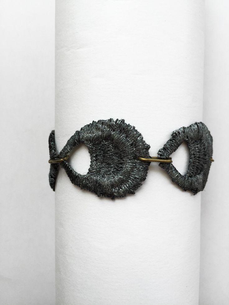 Brazalete sencillo de estilo victoriano, hecho en encaje color gris. Cierre rematado con un cristal checo blanco.