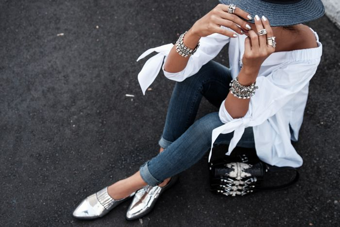 spring / summer - street style - street chic style - summer outfits - casual outfits - travel outfits - getaway outfits - white off shoulder top + skinny jeans + silver loafers + black straw floppy hat + black shoulder bag