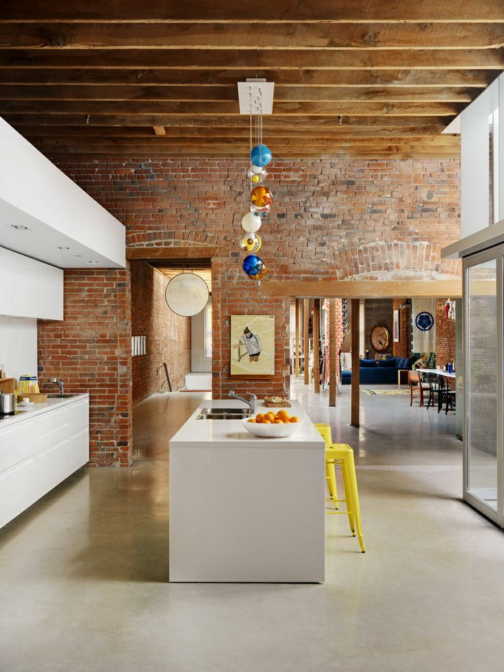 Cement floors, exposed brick and beams, sleek white kitchen, yellow stools.. Can it GET any better?!