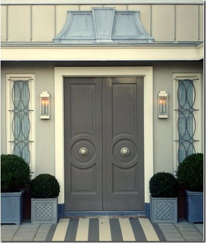 I like the tall planters on the outside and the shorter ones on the inside!  Exterior front door, portico is framed by Art Deco inspired iron work and Parisian style lintel in a variation of stone neutrals. Loving the striped door mat