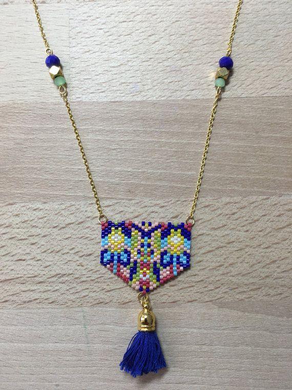 Motif exclusif pour ce tissage créé par Marie AFDMT. Tissage de perles Miyuki Delica en verre, aux couleurs Pop Art, selon la méthode Peyote. Taille du pendentif : 3.5 cm de large sur 3.7 cm de haut Le pendentif est terminé par un pompon bleu roi (hauteur 2.5cm) Il est monté sur une chaîne en laiton sur laquelle vient sintercaler des perles donuts en verre bleu roi et vert deau, et une perle en métal doré. Hauteur total du collier (du mousqueton de fermeture au bas du pompon : 28 cm Lon...